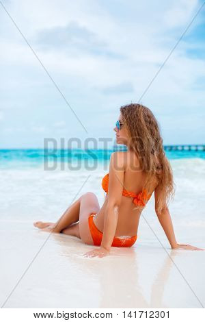 Happy young  woman with long blonde hair,a beautiful smile and white straight teeth,sits on the white sand of a tropical beach near the blue ocean,wearing a bikini is orange,wears blue mirrored sun glasses,ears wearing gold earrings
