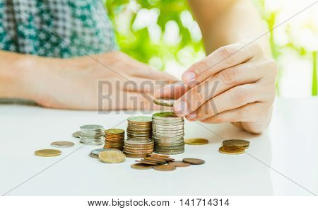Hand Putting Coin On Coins Stack With City Background. Savings, Finance , Business Investment Growth