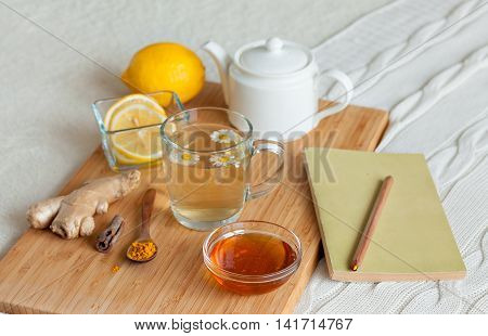 Herbal tea in glass cup with flowers of chamomile, turmeric and honey on a wooden board. Treatment with a cold drink. Treatment of folk remedies in bed. Book reading