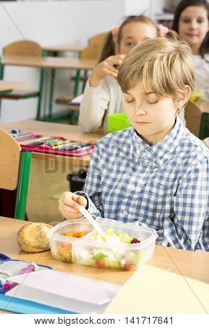 Boy in checked shirt not willing to eat his packed lunch