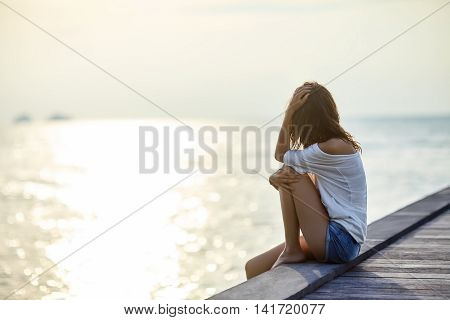 Young Beautiful Woman Sitting On The Pier Enjoying Sunset