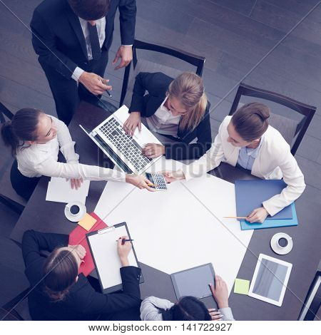 Business workplace with people cup of coffee digital tablet smartphone papers and various office objects on table