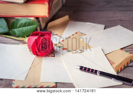 Vintage envelopes red rose and sheets of paper scattered on the wooden table for writing romantic letters.