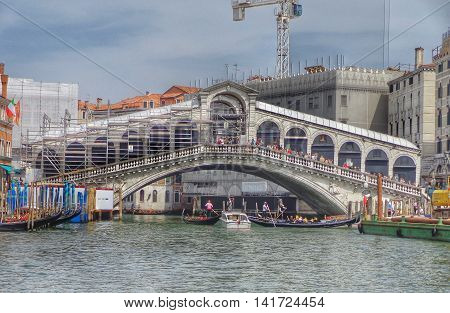 VENICE - April16 2015: Rialto Bridge (Ponte Di Rialto) on a cloudy day on April 16 2015 in Venice. It's oldest and one of the four bridges spanning the Grand Canal in Venice.