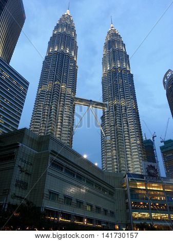 KUALA LUMPUR MALAYSIA - 10 Dec 2013: Petronas twin towers at day light on the cloudy sky background on 10 Dec 2013. Twin towers is the one of the highest buildings in South East Asia and the most famous symbol of Kuala Lumpur.