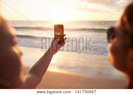 Women Photographing Sunset With Smart Phone On The Beach