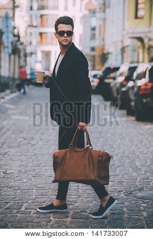 Handsome on the go. Full length of handsome young man in smart casual wear carrying bag and looking over shoulder while walking at the street
