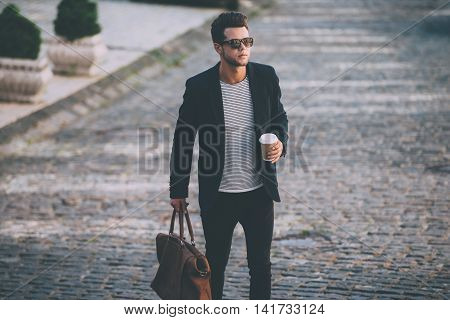 Stylish handsome on the go. Handsome young man in smart casual wear carrying bag and coffee cup while walking along the street