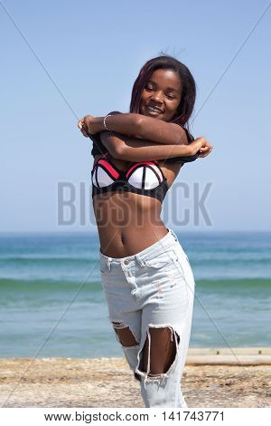 Beautiful african woman in jeans taking her top off and exposing her bikini at the beach