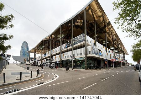 Barcelona Spain - April 4 2016: View to the Tower Agbar skyscraper and Mercat dels Encants. Mercat dels Encants is a Barcelona's largest and best known flea market. One of the oldest flea markets in Europe and Spain