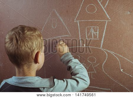 A little boy draws with chalk on a blackboard a drawing lesson at school back to school