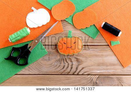 Halloween mini pumpkin decor. Orange felt pumpkin toy, scissors, flat pieces of felt, green and black thread, needle, paper template on wood background. Halloween sewing crafts