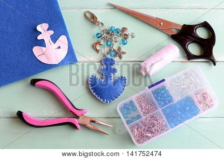 Blue felt anchor key chain with beads. Hand made charm keychain for beach bags, scissors, pliers, a box of beads, white thread, needle, paper pattern, pin on wood background. Summer sewing DIY concept