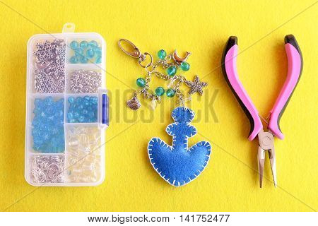 Blue felt anchor key chain with beads and metal pendants. Home made charm keychain for beach bags, scissors, pliers, box with different materials on yellow flat piece of felt. Craft hobby background