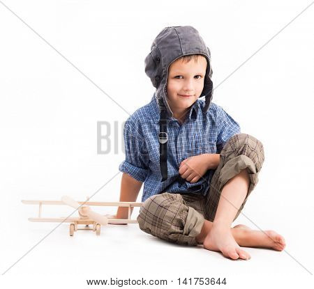 little boy with pilot hat and toy airplane sitting isolated on white background