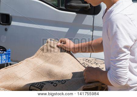Saint Hilaire de Riez France - July 31 2016 : a young man looks old coffee bags burlap for a outdoor flea market