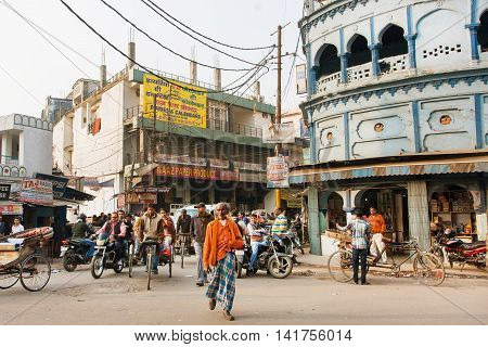 LUCKNOW, INDIA - JAN 31, 2013: Poor people walking on indian street with blue houses and bikes driving around on January 31, 2013. Lucknow with population of 6000455 is the largest city of Uttar Pradesh