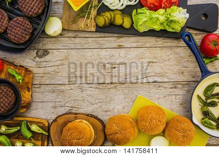Ingredients for cooking burgers. Raw ground beef meat cutlets on wooden board, onion, greens, pickles, tomatoes, sauce, background