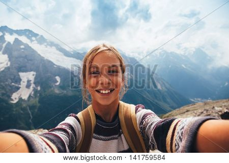 Pre teen girl taking selfie photo on the top of the mountain, autumn hike with backpacks, alpine view