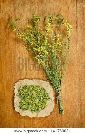 Melilot.Dried herbs for use in alternative medicine.Herbal medicine phytotherapy medicinal herbs.For preparation of infusions decoctions tinctures powders ointments tea.Background wooden board