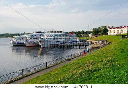 UGLICH RUSSIA - JULY 19 2016: Unidentified people walk along promenade of old Russian town of Uglich. Cruise ship