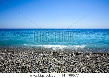 Blue sea and horizon with wave gently breaking on beach