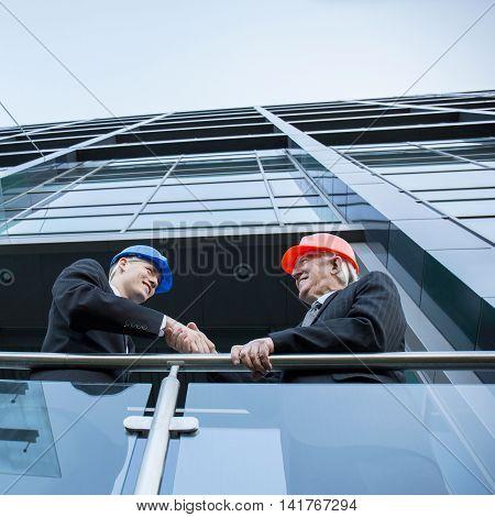 Engineers during handshake on the balcony horizontal