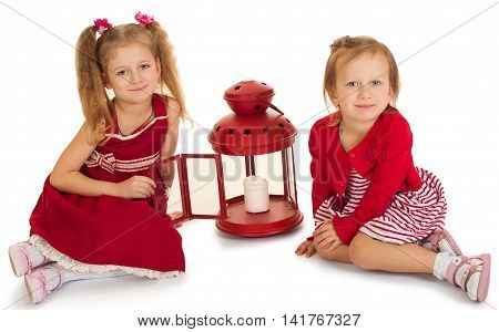 Two beautiful little girls sisters dressed in red dresses . girl sitting on the floor near the lantern in which the candle burns - Isolated on white background