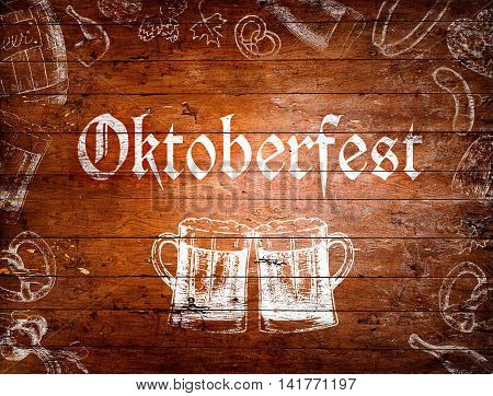Oktoberfest sign, two beer mugs and various symbols. Chalk drawings on wooden background. Studio shot.