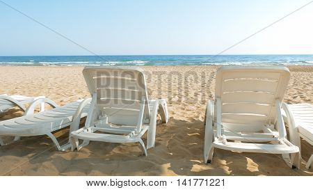 White chairs are placed on the beach for people to relax or sunbath. Beaches make a wonderful vacation spot. One of the most beautiful sceneries.