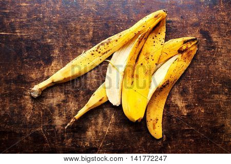 A branch of rotten ripe bananas peel on vintage wooden background. Over ripe peeled banana close up. Out of Date food