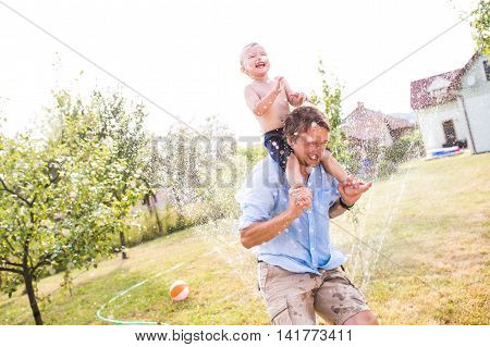 Father carrying his son on his shoulders at the sprinkler, fun in garden, sunny summer day, back yard