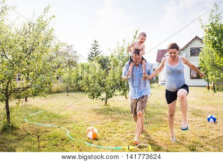 Little boy with mother and father at the sprinkler, fun in garden, sunny summer day, back yard