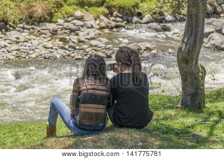 CUENCA, ECUADOR, NOVEMBER - 2015 - Two girls sitting at grass in front of river watching the cellphone in Cuenca Ecuador