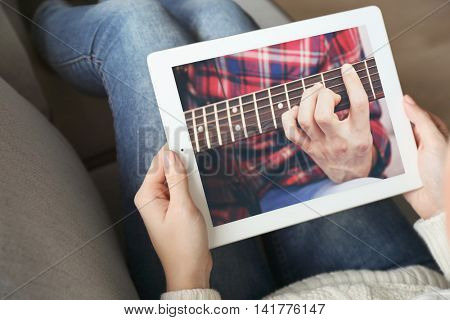 Female hands holding PC tablet on home interior background.