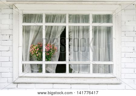 The horizontal white window with curtains a bouquet of flowers on the windowsil