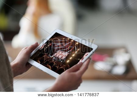 Woman's hand tablet on blurred background using. Spotlight with laser rays on screen