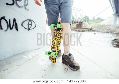 young handsome real hipsrter guy staying under the bridge extreeme with leopard skateboard, lifestyle people concept close up, only legs part