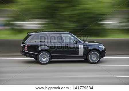 Land Rover Range Rover on the highway with blurred background.