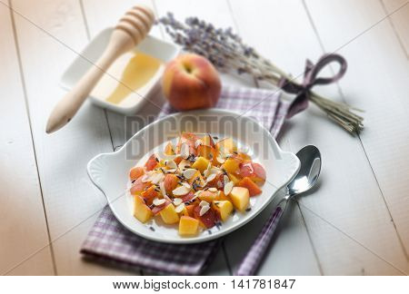 fruit salad with peach almond honey and lavender flowe, selective focus
