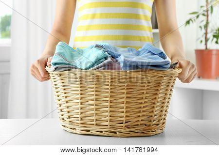 Woman holding wicker basket in laundry