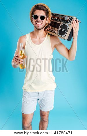 Smiling handsome young man in hat and sunglasses with boombox and bottle of beer over blue background
