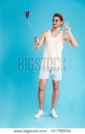 Cheerful young man in hat and sunglasses taking selfie with smartphone and monopod over blue background