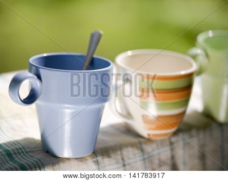 A bunch of tea mugs standing in a row on a clean kitchen towel selective focus closeup