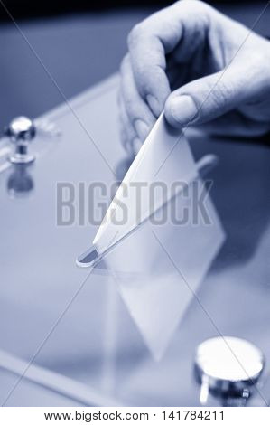 Image of a ballot box and hand putting a blank ballot insideelections voting concept blue toned