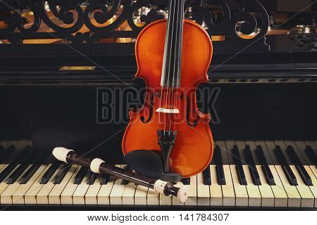 Flute and violin on piano keys