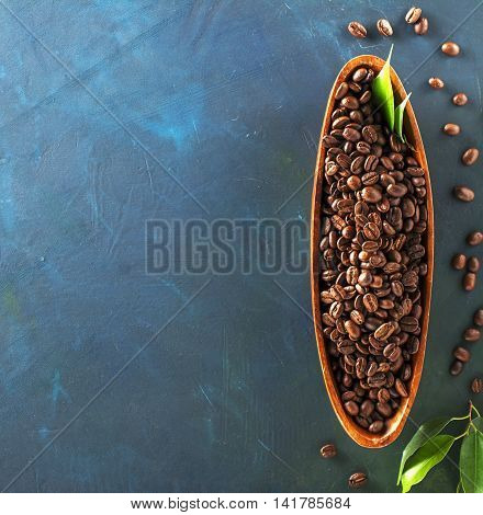 Wooden plate in the form of boats full of dark aromatic coffee beans on a colorful blue-green background. Top view