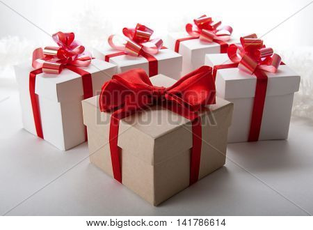 one large gift box and white gift boxes on a wood background