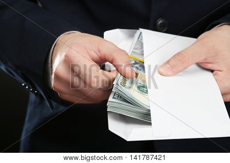 Businessman with money in envelope. Corruption concept