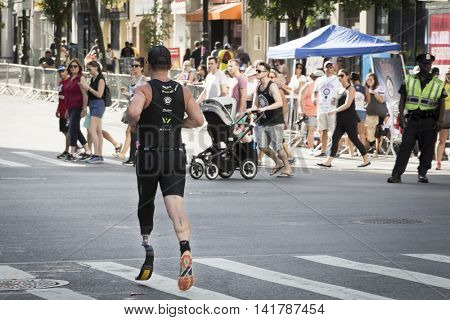 NEW YORK CITY -  JULY 24 2016:: ParaTriathlete running in the NYC Triathlon Race on West 72nd St in New York. The run is 10k and the race is the only International Distance triathlon in the city.